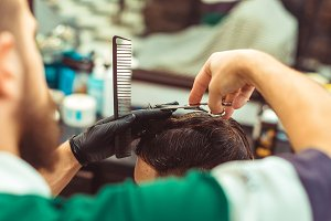 Barber using scissors and comb.