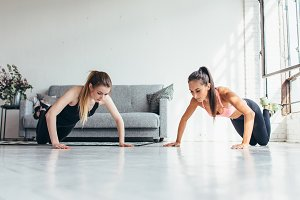Two fit women doing push up exercise at home