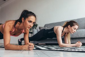 Two fit women standing in plank position on floor at home