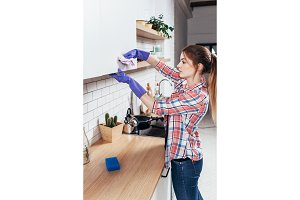 Young woman cleaning, wiping kitchen furniture at home