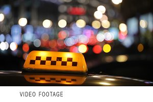 Illuminated taxi cab sign on a city
