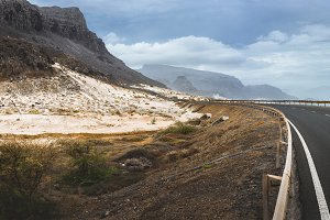 Winding road leads along breathtaking coastline past black volcano and white sand dunes. North of Calhau, Sao Vicente Island Cape Verde