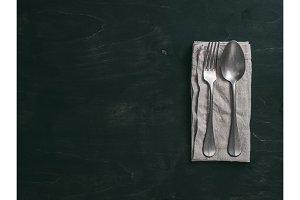 Vintage cutlery on dark background, copy space