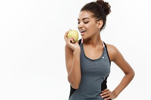 Healthy and Fitness concept - Beautiful American African lady in grey fitness clothes eating green apple. Isolated on white background.