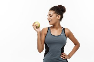 Healthy and Fitness concept - Beautiful American African lady in grey fitness clothes holding green apple. Isolated on white background.