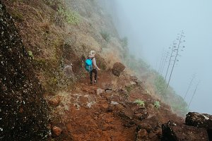 Hiker women with backpack walking down the steep slope of the rock in the foggy mountains.