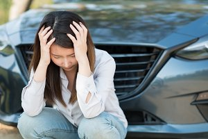 Woman sitting at car broken down
