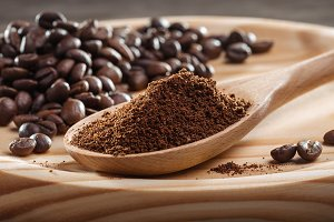 Ground coffee in spoon. Coffee beans