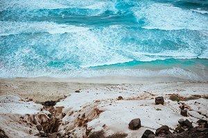 Quaint view of azure roaring ocean, black volcanic stones and massive sand dunes along the coast. North of Calhau, Sao Vicente Island Cape Verde