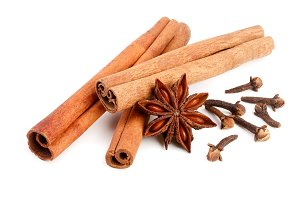 Cinnamon sticks with star anise and clove isolated on white background. Top view