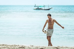 Guy playing football on the beach