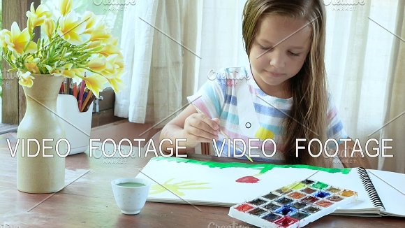 Child Soaking Paintbrush In To Color And Drawing Near Window