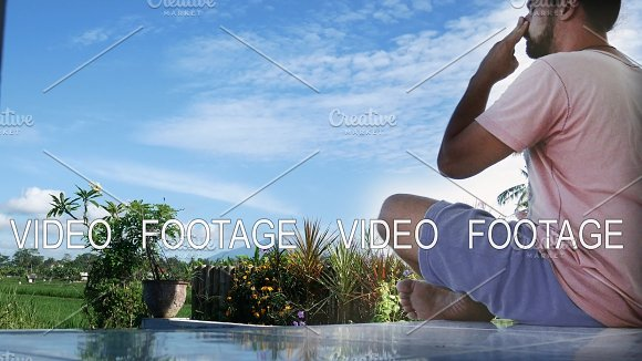 Man Sitting In Yoga Lotus Pose At Green Grass In The Meadow And Meditates