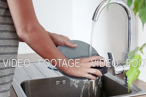 Woman washing plate in kitchen sink