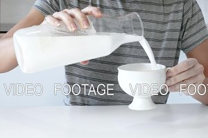 Close up female hand pouring milk into cup on table