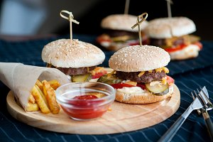 Burger, hamburger with french fries, ketchup, mustard and fresh vegetables on a cutting wooden board