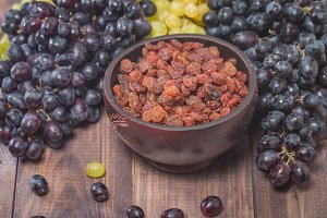 Raisins in bowl and grapes