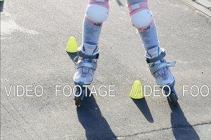 Little girl roller skating between cones