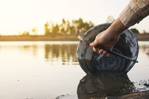 woman holding a bucket on lake