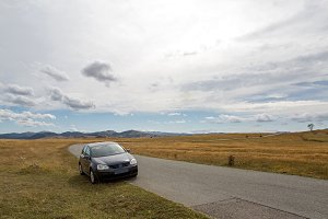 car with the traveler stands on the roadside in a yellow field in zabljak in Montenegro