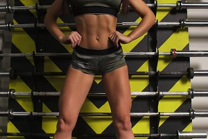 A beautiful sporty brunette is standing in the gym next to the barbells