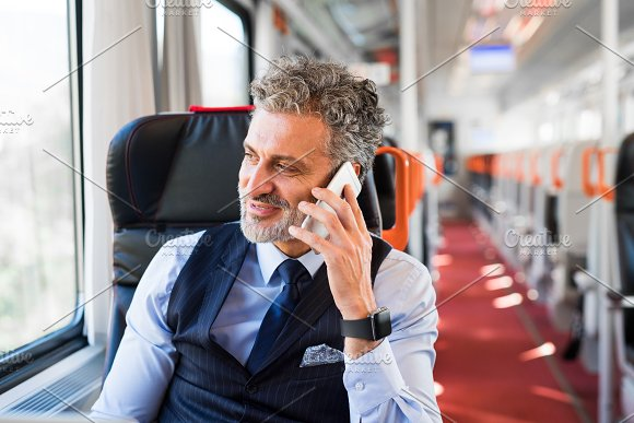 Mature Businessman With Smartphone Travelling By Train