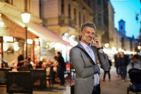 Mature Businessman With A Smartphone In A City