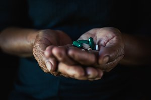 old woman holding a pill