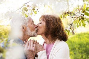 Senior couple in love outside in spring nature kissing.