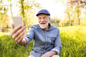 Senior man with smartphone outside in spring nature.