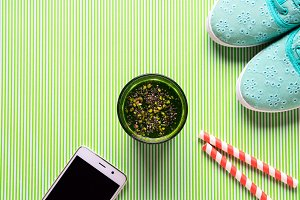 Green smoothie, girl's shoes and smartphone