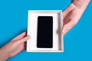 hands passing smart phone in box