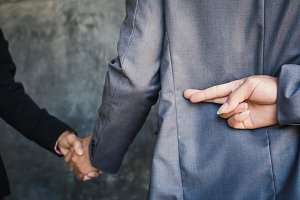 Businessman shake hand and betray