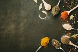 Spices and herbs over black stone