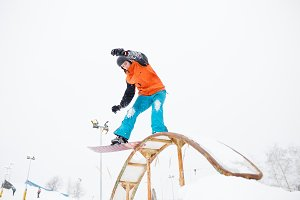 Photo of young sportive man skiing on snowboard with springboard