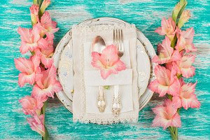 Tableware and pink gladiolus