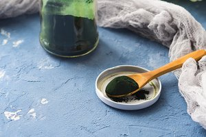 Spirulina powder on blue background