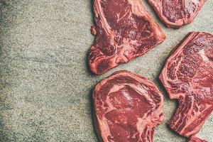 Porterhouse, t-bone and rib-eye steaks over grey background, copy space