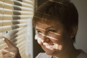 Middle-aged woman standing in front of a window in daylight, a shade of blinds on her face