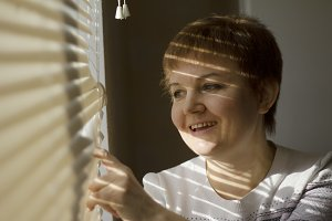 Middle-aged woman standing in front of a window in daylight, dreaming and smiling, a shade of blinds on her face