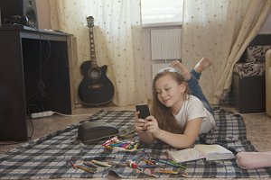 Girl teen who spend time at home drawing sketches in a notebook and using her smartphone while lying on the floor
