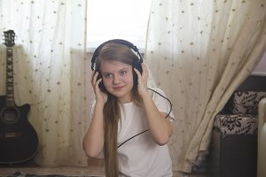 Teen girl listening to music in headphones at home
