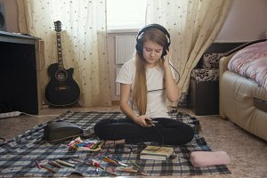 Teen girl listening to music in headphones using smartphone sitting on the floor at home