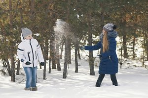Two teenage girls in warm clothes playing snowballs between the trees in the winter