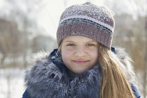 Portrait of teen girl in cap and jacket with fur collar in winter covered by snow
