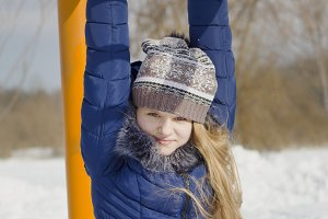 Teen girl wearing warm clothes playing outside in the winter, using the horizontal bar