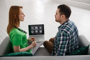 Female doctor and male patient looking at MRI concept healthcare, medical and radiology concept