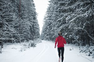 Female jogging in winter forest