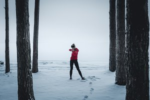 Female working out in winter forest