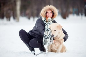 Image of girl in black jacket squatting next to dog in winter